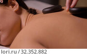 Купить «beautiful woman having hot stone massage at spa», видеоролик № 32352882, снято 19 октября 2019 г. (c) Syda Productions / Фотобанк Лори