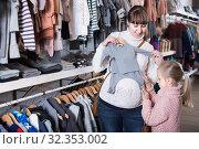 Купить «Pregnant mother and daughter choosing romper suit for baby in children's clothes shop», фото № 32353002, снято 10 января 2017 г. (c) Яков Филимонов / Фотобанк Лори