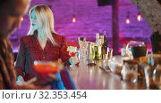 Купить «Gorgeous blonde young woman sitting by the bartender stand - drinking a beverage from the straw - a man sitting in his phone on the foreground», видеоролик № 32353454, снято 5 июля 2020 г. (c) Константин Шишкин / Фотобанк Лори