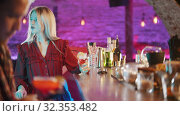 Купить «Gorgeous blonde young woman sitting by the bartender stand - drinking a beverage from the straw - a man sitting in his phone on the foreground and drinking», видеоролик № 32353482, снято 5 июля 2020 г. (c) Константин Шишкин / Фотобанк Лори