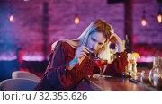 Купить «Gorgeous bored young woman sitting by the bartender stand and stirs the drink with a straw», видеоролик № 32353626, снято 19 февраля 2020 г. (c) Константин Шишкин / Фотобанк Лори