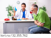 Old man visiting young male doctor gastroenterologist. Стоковое фото, фотограф Elnur / Фотобанк Лори
