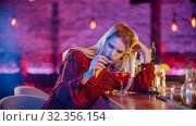 Gorgeous bored young woman sitting by the bartender stand and stirs the drink with a straw. Стоковое фото, фотограф Константин Шишкин / Фотобанк Лори