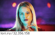 Gorgeous blonde young woman holding a straw from the beverage and looking in the camera - neon blue lighting. Стоковое фото, фотограф Константин Шишкин / Фотобанк Лори