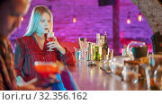 Купить «Gorgeous blonde young woman sitting by the bartender stand - drinking a beverage from the straw - a man sitting in his phone on the foreground», фото № 32356162, снято 27 мая 2020 г. (c) Константин Шишкин / Фотобанк Лори
