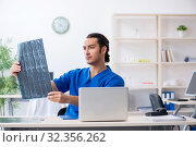 Купить «Young male doctor working in the clinic», фото № 32356262, снято 21 июня 2019 г. (c) Elnur / Фотобанк Лори