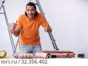 Купить «Young man contractor doing renovation at home», фото № 32356402, снято 4 июня 2019 г. (c) Elnur / Фотобанк Лори