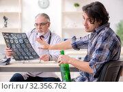 Купить «Young male alcoholic visiting old doctor», фото № 32356762, снято 3 апреля 2019 г. (c) Elnur / Фотобанк Лори