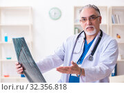 Купить «Old male doctor working in the clinic», фото № 32356818, снято 15 марта 2019 г. (c) Elnur / Фотобанк Лори