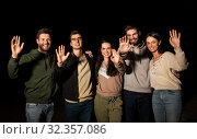 happy smiling friends waving hands at night. Стоковое фото, фотограф Syda Productions / Фотобанк Лори