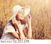 Купить «happy young woman in sun hat on cereal field», фото № 32357278, снято 31 июля 2016 г. (c) Syda Productions / Фотобанк Лори