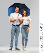 Купить «happy couple in white t-shirts with umbrella», фото № 32357418, снято 6 октября 2019 г. (c) Syda Productions / Фотобанк Лори