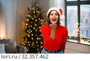Купить «woman in santa hat sending air kiss on christmas», фото № 32357462, снято 30 сентября 2019 г. (c) Syda Productions / Фотобанк Лори