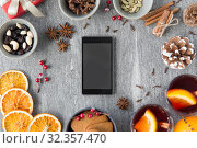Купить «smartphone, hot mulled wine and christmas spices», фото № 32357470, снято 4 октября 2018 г. (c) Syda Productions / Фотобанк Лори