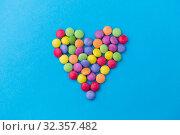 Купить «candy drops in shape of heart on blue background», фото № 32357482, снято 11 декабря 2018 г. (c) Syda Productions / Фотобанк Лори