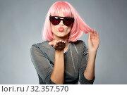 Купить «woman in pink wig and sunglasses sending air kiss», фото № 32357570, снято 30 сентября 2019 г. (c) Syda Productions / Фотобанк Лори