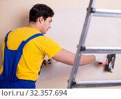 Купить «Young contractor employee applying plaster on wall», фото № 32357694, снято 15 марта 2018 г. (c) Elnur / Фотобанк Лори