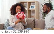 Купить «happy couple with bunch of flowers kissing at home», видеоролик № 32359990, снято 17 октября 2019 г. (c) Syda Productions / Фотобанк Лори