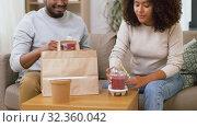 Купить «couple with takeaway food and straw drinks at home», видеоролик № 32360042, снято 17 октября 2019 г. (c) Syda Productions / Фотобанк Лори