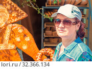 Russia, Samara, July 2019: An attractive mature woman stands near a tray with curly baked goods at a gastronomic festival. Стоковое фото, фотограф Акиньшин Владимир / Фотобанк Лори