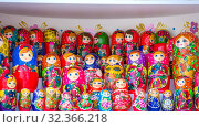 Russian souvenirs. Multi-colored nesting dolls stand on shelves at an exhibition for sale. (2019 год). Редакционное фото, фотограф Акиньшин Владимир / Фотобанк Лори