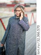 Женщина средних лет на улице разговаривает по мобильному телефону. Стоковое фото, фотограф Игорь Низов / Фотобанк Лори