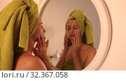 Beautiful woman take care of her face against mirror in bathroom. Стоковое видео, видеограф Яков Филимонов / Фотобанк Лори