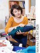 Купить «Woman looking for cloth in shop», фото № 32367626, снято 7 февраля 2019 г. (c) Яков Филимонов / Фотобанк Лори