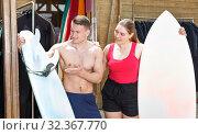 Купить «Woman taking for rent surf equipment», фото № 32367770, снято 30 апреля 2018 г. (c) Яков Филимонов / Фотобанк Лори