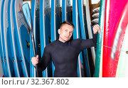 Portrait of sports young man in wetsuit holding paddle in surf club. Стоковое фото, фотограф Яков Филимонов / Фотобанк Лори