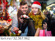 Купить «Joyful young couple in Christmas hat delighted with purchases», фото № 32367962, снято 14 декабря 2017 г. (c) Яков Филимонов / Фотобанк Лори