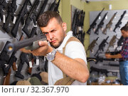 Купить «Portrait of male customer which is choosing air-powered gun», фото № 32367970, снято 4 июля 2017 г. (c) Яков Филимонов / Фотобанк Лори