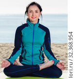 Купить «Girl practicing yoga cross-legged in morning by sea», фото № 32368954, снято 10 апреля 2017 г. (c) Яков Филимонов / Фотобанк Лори