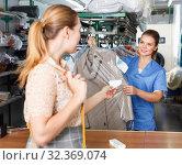 Купить «Young woman working with client in modern laundry, returning clothing after dry cleaning», фото № 32369074, снято 9 мая 2018 г. (c) Яков Филимонов / Фотобанк Лори