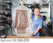 Купить «girl worker offering professional dry cleaning,», фото № 32369078, снято 9 мая 2018 г. (c) Яков Филимонов / Фотобанк Лори