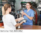 Купить «Woman receiving clothing for dry cleaning», фото № 32369082, снято 9 мая 2018 г. (c) Яков Филимонов / Фотобанк Лори