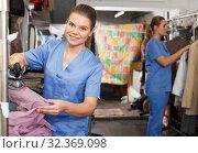 Купить «Happy girl ironing clothes at dry cleaning», фото № 32369098, снято 9 мая 2018 г. (c) Яков Филимонов / Фотобанк Лори