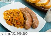 Купить «Sausages with braised cabbage», фото № 32369290, снято 17 ноября 2019 г. (c) Яков Филимонов / Фотобанк Лори