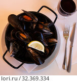 Купить «Image of delicious steamed mussels on pan with lemon», фото № 32369334, снято 12 ноября 2019 г. (c) Яков Филимонов / Фотобанк Лори