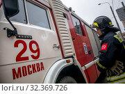 Купить «Сотрудник пожарного расчета обеспечивает пожарную безопасность во время публичной акции в городе Москве, Россия», фото № 32369726, снято 4 ноября 2019 г. (c) Николай Винокуров / Фотобанк Лори