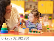 Купить «Woman with child talking and smiling while playing educational toys together in daycare centre», фото № 32382850, снято 26 мая 2020 г. (c) Оксана Кузьмина / Фотобанк Лори