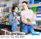 glad girl chatting on screen tablet and choosing literature books with mother. Стоковое фото, фотограф Яков Филимонов / Фотобанк Лори