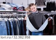 Купить «Girl choosing jeans in store», фото № 32382958, снято 21 марта 2018 г. (c) Яков Филимонов / Фотобанк Лори