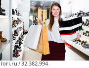 Купить «Portrait of young woman which is showing purchases in shoes store.», фото № 32382994, снято 13 декабря 2017 г. (c) Яков Филимонов / Фотобанк Лори