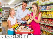 Купить «family of three choosing food in the grocery shop», фото № 32383118, снято 11 июля 2017 г. (c) Яков Филимонов / Фотобанк Лори