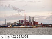 Sunila pulp and paper mill of Stora Enso Oyj corporation on shore of Gulf of Finland. Red brick industrial buildings and smoking chimneys. Редакционное фото, фотограф Юлия Бабкина / Фотобанк Лори
