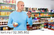 Купить «Focused man choosing fresh products during shopping at food store», фото № 32385802, снято 4 июля 2018 г. (c) Яков Филимонов / Фотобанк Лори