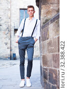 Купить «young European guy in shirt and trousers with suspenders walking around city», фото № 32388422, снято 27 июня 2018 г. (c) Татьяна Яцевич / Фотобанк Лори