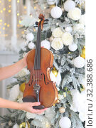Купить «girl's hands hold a violin on the background of the New Year tree», фото № 32388686, снято 6 ноября 2019 г. (c) Марина Володько / Фотобанк Лори