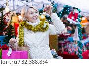 Smiling woman is buying toys for X-mas tree in the market. Стоковое фото, фотограф Яков Филимонов / Фотобанк Лори